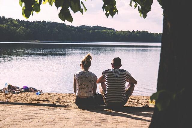 川辺でくつろぐカップル